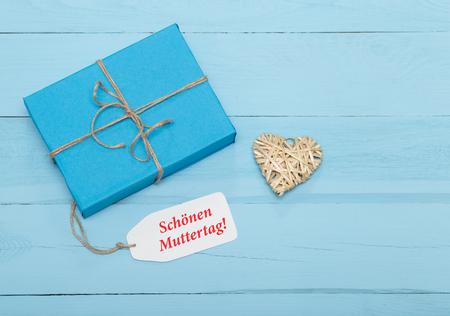 agradecimiento: Tarjeta del día de madres con el regalo del corazón índigo y paja sobre fondo azul Foto de archivo