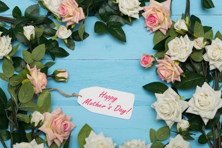 agradecimiento: Tarjeta del d�a de madres con las rosas r�stico en el fondo de madera azul