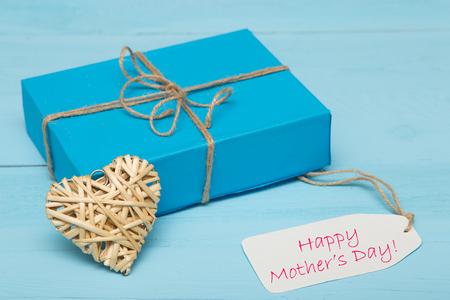 agradecimiento: caja de regalo de color azul con una tarjeta de coraz�n d�a paja y madres en el fondo de madera azul Foto de archivo