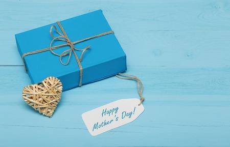agradecimiento: caja de regalo de color azul con una tarjeta de corazón día paja y madres en el fondo de madera azul Foto de archivo