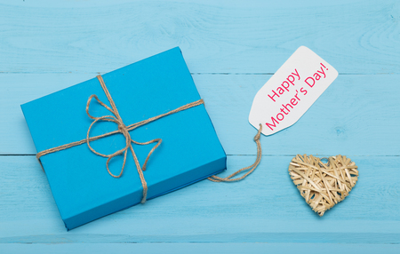 blue gift box with a straw heart and mothers day card on wooden blue background