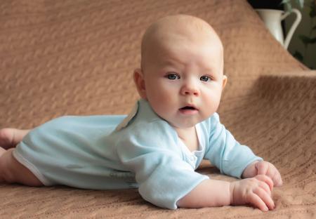 Bebé bonito de quatro meses na cama, conceito do dia de mãe