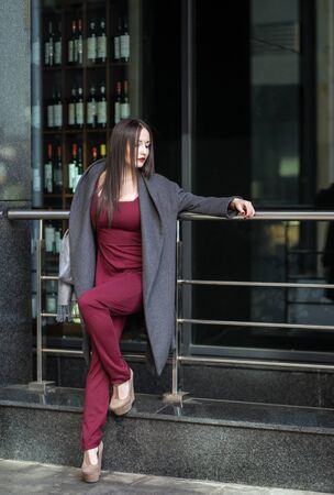 overall: Chic brunette woman in marsala overall standing in the street watching to the right