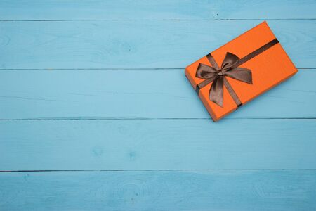christmas bonus: orange gift box with brown bow on a blue wooden background Stock Photo