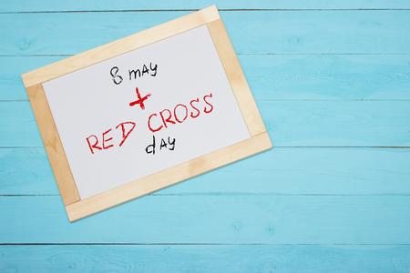 red cross: Ocho de mayo D�a mundial de la Cruz Roja, las letras en el escritorio blanco, fondo azul