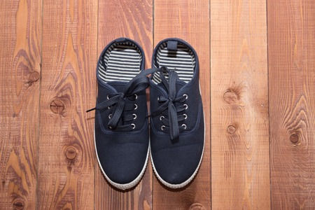 laid: Pair of dark blue running shoes laid on a wooden floor background Stock Photo