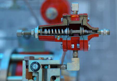 regulator: Industrial gas pressure regulator cut, red color, blue background Stock Photo