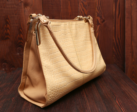 designer bag: new stylish womens beige leather handbag. Glossy bag on the wooden background