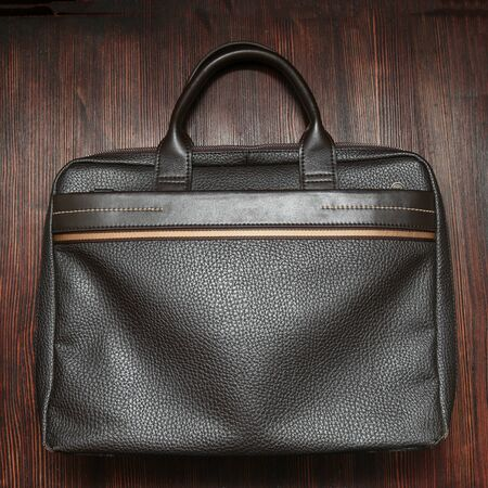 leasure: Mans new brown leasure bag on wooden background