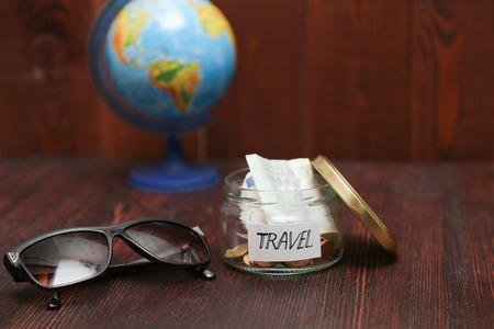 holiday budget: Collecting money for travel. Glass jar as moneybox with cash savings, paper label on wooden table. Sunglasses, and globe at background