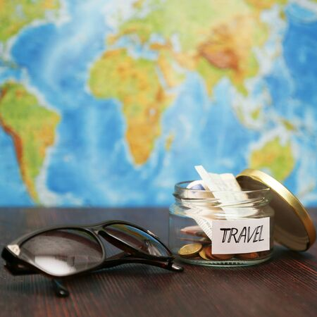 holiday budget: Travel money in glass jar, brown sunglasses, world map at the background.