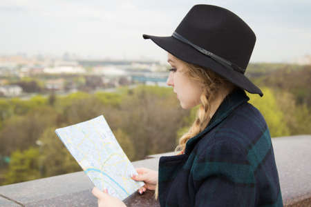 sightseeng: Cute blonde woman in black hat looking at sightseengs map, while standing at observation deck. Stock Photo