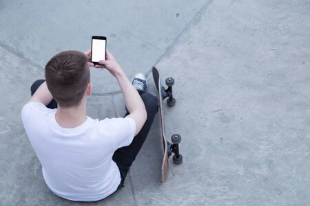 skate board: Young man in white t-shirt and black jeans sitting near skate board using smart phone, copy space for your text