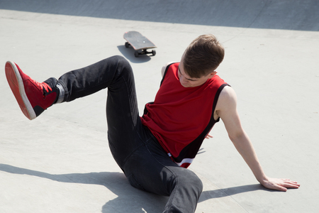 off ramp: Young man fall off the skate board, sitting on concrete ramp.