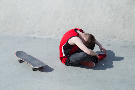 skate board: Young man fall off the skate board, sitting on concrete ramp.