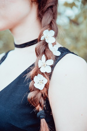 tress: Close up view of young womans tress with cherry flowers within, vintage style photo
