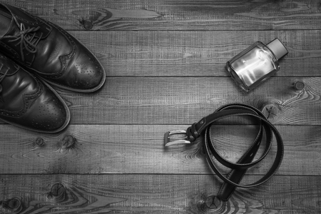 chrome man: Black and white picture of mans business accessories: oxford shoes, belt and parfume. Top view.