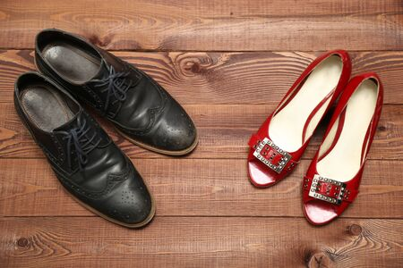 woman sandals: Classic man shoes and red woman sandals on brown wooden background