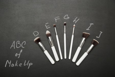 make up brushes: Set of make up brushes on black background with chulk pictures. ABC of make up concept.