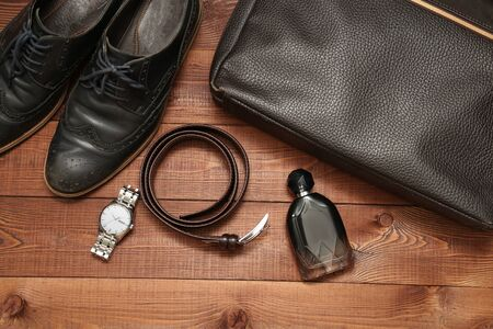 mans watch: Collection of mans business accessories and clothes. Classic shoes, lether belt, watch, bag and perfume on wooden background.