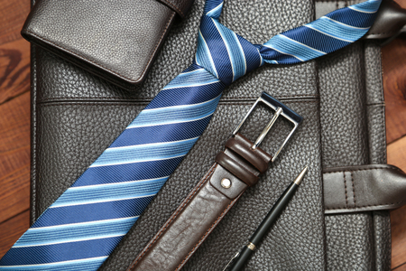 mans watch: Collection of mans business accessories and clothes. Classic shoes, lether belt, watch, bag and parfume on wooden background. Stock Photo