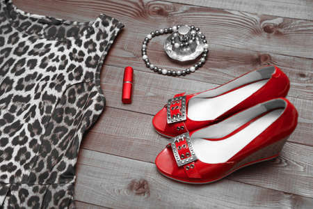 Bright red high hilled shoes and lipstick on sepia wooden background
