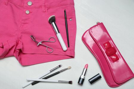 clutch bag: Assorted set of make up brushes and tools on pink jeans shorts, fuchia clutch on white wooden background