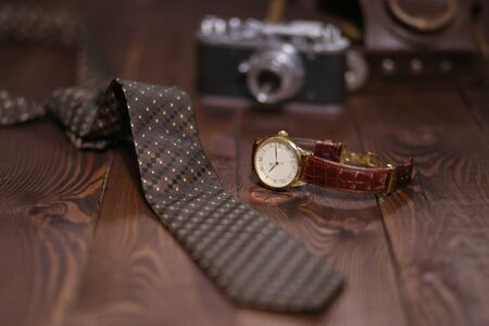 Flat lay shot of Men fashion accessories. Brown watch, tie, and retro camera on wooden background. Still life. Business look. Stock Photo