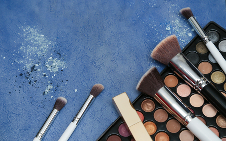lip pencil: Collection of makeup products on blue textured background with copyspace Stock Photo