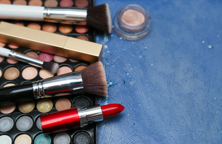 loose skin: Collection of makeup products on blue textured background with copyspace Stock Photo