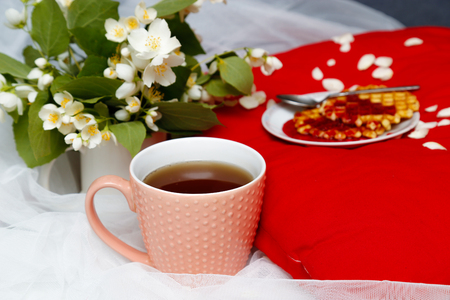 Breakfast in bed -tea and biscuits with strawberry jam on red pillow, jasmine flowers Stock Photo
