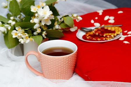 desayuno romantico: Desayuno en la cama -te y galletas con mermelada de fresa en la almohadilla roja, flores de jazmín Foto de archivo