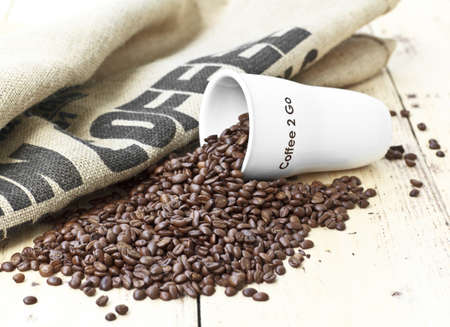 to go cup: white coffee cup  on jute background with Coffee beans Stock Photo