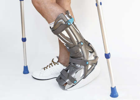 Man with a broken leg with Orthotic on a white background photo