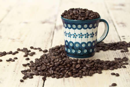 coffee cup  on  old wooden table with Coffee beans