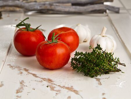 сooking: Tomatoes, garlic and thyme on a white wooden table