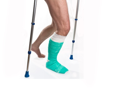 jambe cass�e: L'homme avec une jambe cass�e avec des b�quilles et un bandage sur un fond blanc