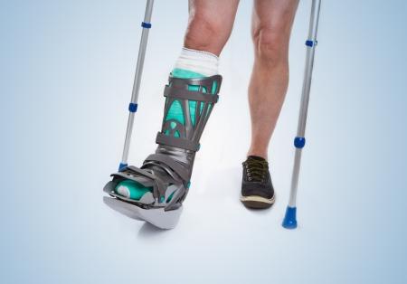 fractura: Hombre con una pierna rota con muletas y vendaje sobre un fondo azul