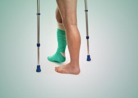 jambe cass�e: L'homme avec une jambe cass�e avec des b�quilles et bandage sur un fond blanc