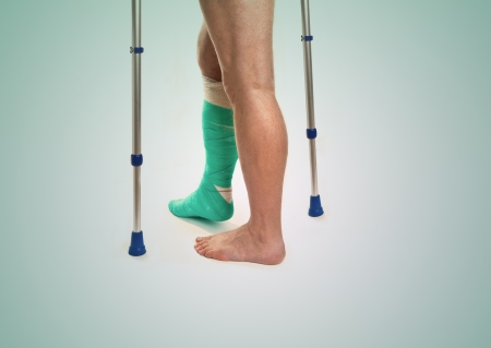Man with a broken leg with Crutches and bandage on a white background  photo