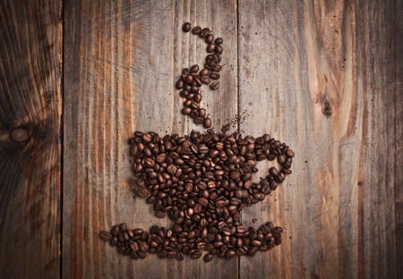 Coffee beans in cup shape on the old wooden  background photo