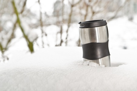 Cup of hot drink outdoors in the snowy winter