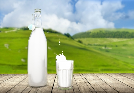 Full glass and bottle of milk on wooden table outdoor  photo