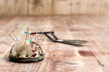 Vintage Background with sewing tools,  Scissors, pincushion and needles on the old wooden background Stock Photo