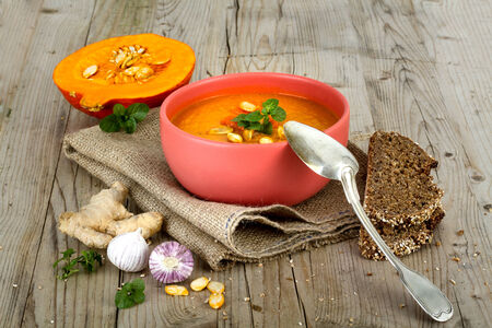 Vegetable Cream Soup in the Bowl with seeds and rustic Bread Stock Photo