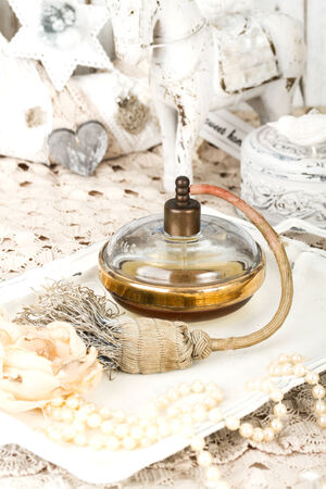 Antique glass scent bottle on ladies dressing table with shabby schic pearl necklace and laces photo
