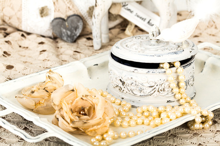 antique jewelry box with pearls on ladies dressing table with shabby schic pearl necklace and lace Stock Photo