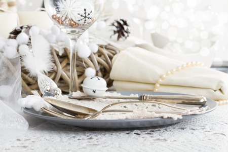 Beautifully set table in white shabby chic for Christmas Eve