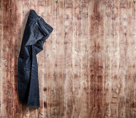 jeans fabric: Blue jeans trouser over old grungy wood planks background