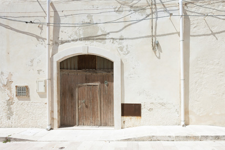 Vieste, Apulia, Italy - A folding gate, two rainwater pipes and some cables Standard-Bild - 101058051